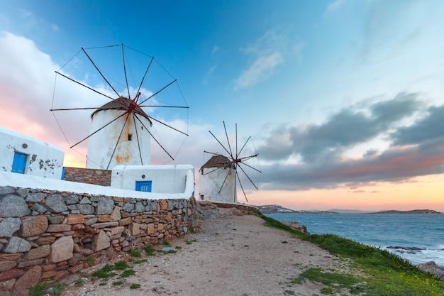 Molinos de viento blancos tradicionales al amanecer, mykonos, grecia