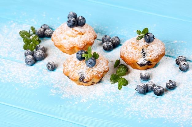 Mollete cocido hecho en casa con los arándanos, bayas frescas, menta, azúcar en polvo en fondo de madera azul.