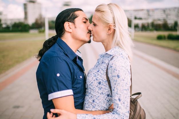 Momento beso de joven pareja en caminata en época cálida del año.