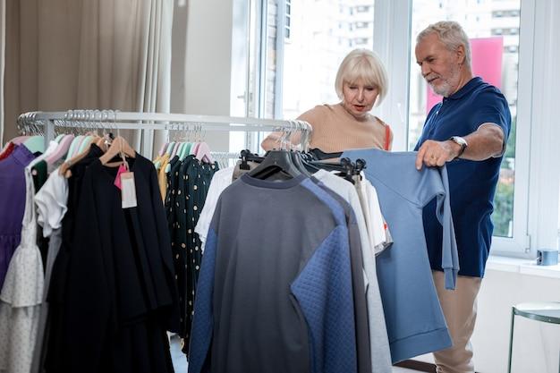 Momento de elección. pareja de ancianos concentrada de pie cerca de perchas con ropa mientras busca un elegante jersey para su hijo