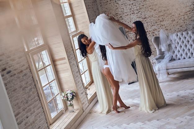 Momento feliz. vista superior de longitud completa de dos mujeres jóvenes atractivas que se ponen un vestido de novia en una novia mientras están juntos cerca de la ventana