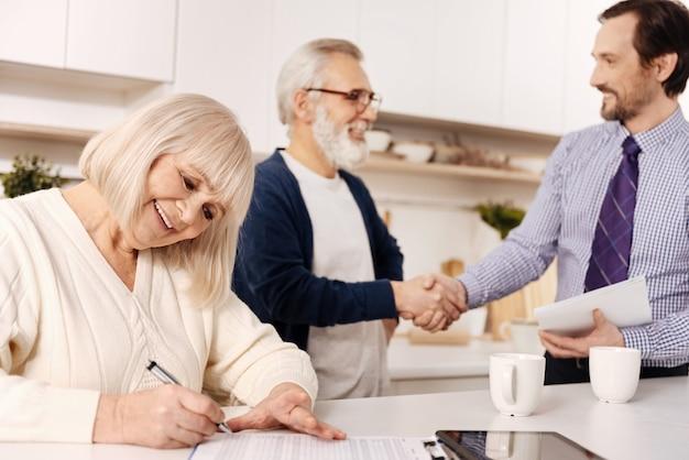 El momento de firmar documentos importantes. encantadora mujer anciana sonriente sentada y firmando contrato mientras su marido saluda al abogado