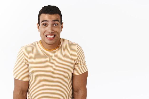 Momento incómodo. chico hispano nervioso lindo, encogiéndose de hombros y sonriendo avergonzado