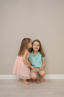 Momentos alegres hermanas sobre fondo beige
