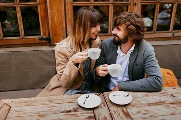 Momentos románticos de una elegante pareja de enamorados sentados en un café, tomando café, conversando y disfrutando del tiempo que pasan juntos.