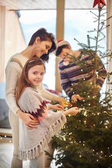 Momia y niña de pie junto al árbol de navidad
