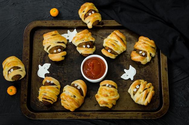 Las momias de halloween albóndigas envueltas en masa con salsa de tomate picante en una vieja bandeja para hornear sobre un fondo negro. idea para fiesta de halloween.