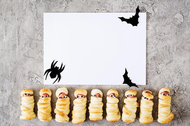 Momias de salchicha aterradora en masa con ojos graciosos en la mesa. decoración de halloween y nota de papel en blanco blanco o tarjeta de felicitación