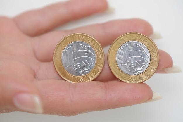 Moneda de 1 real brasileño en una mano de mujer
