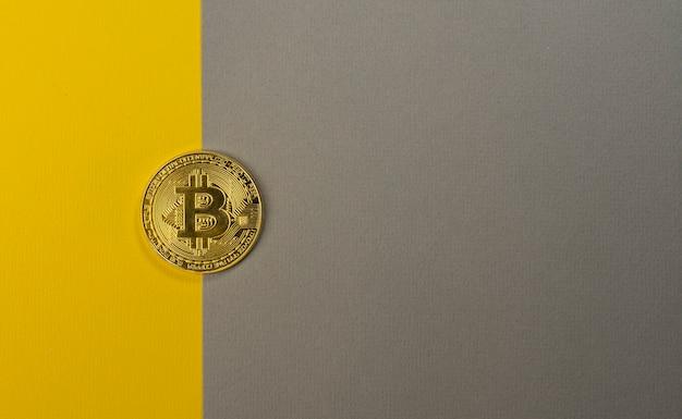 Moneda bitcoin brillante sobre fondo amarillo y gris de moda con espacio de copia