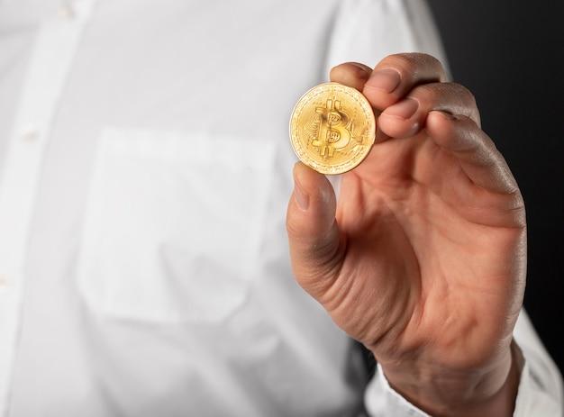 Moneda bitcoin dorada brillante en manos masculinas de cerca.