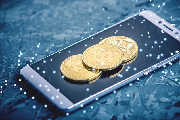 Moneda bitcoin física en la pantalla del teléfono. el concepto de criptomoneda y blockchain