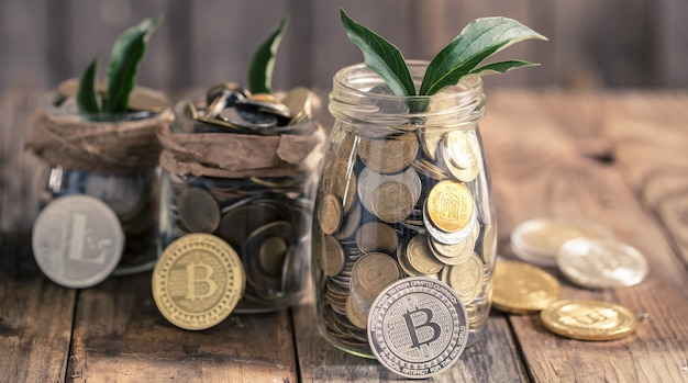 Moneda bitcoin y un frasco con monedas