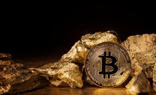 Moneda bitcoin junto a piezas de oro