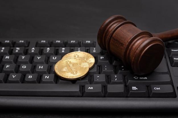Moneda bitcoin con martillo de juez en el teclado. litigio, fraude de criptomonedas en línea.