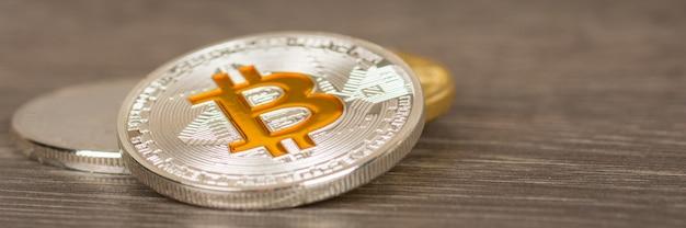Moneda bitcoin metálica plateada en mesa de madera