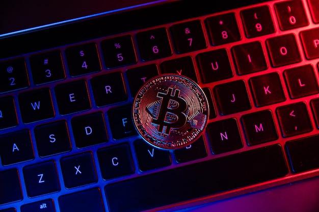 Moneda bitcoin en neón en el teclado del portátil.