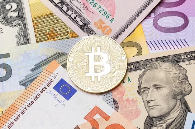 Moneda bitcoin de oro sobre nosotros y billetes de euro. foto de alta resolución.