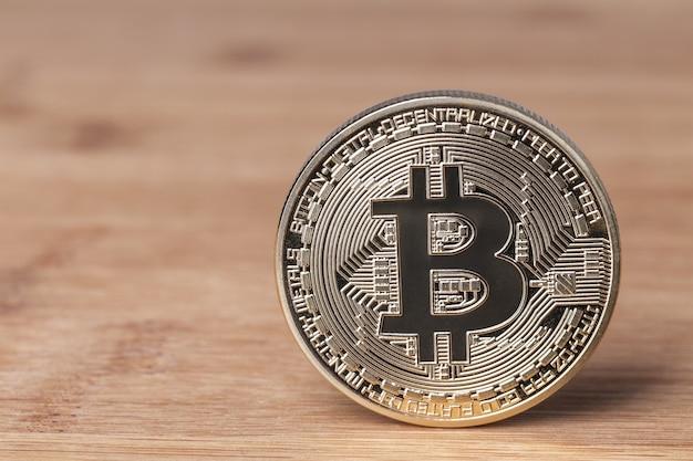 Moneda bitcoin sobre un fondo de madera. moneda criptográfica de cerca.