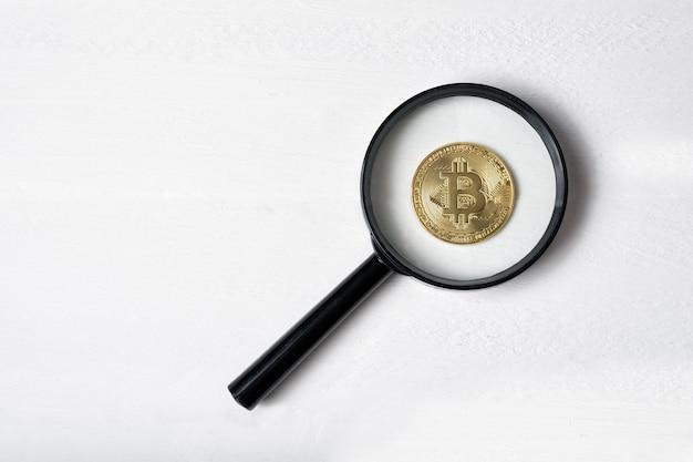 Moneda bitcoin a través de una lupa sobre un fondo blanco.