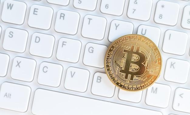 Moneda criptográfica bitcoin de oro en el teclado de la computadora blanca, concepto de criptomoneda virtual