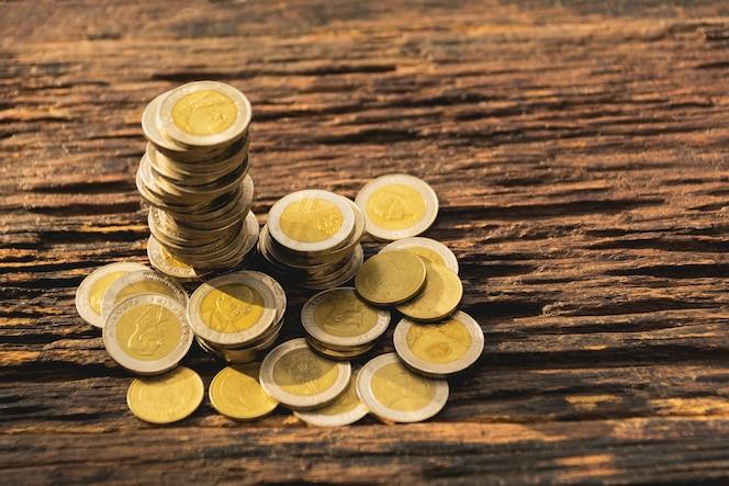 Moneda de la pila del primer en la tabla de madera. concepto financiero y de ahorro.