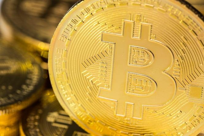 Moneda de primer bitcoin dorado con otras monedas borrosas en el fondo