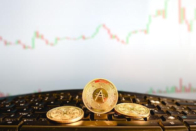 Moneda digital cardano, ada, en monedas de oro, en el teclado de la computadora de un corredor.