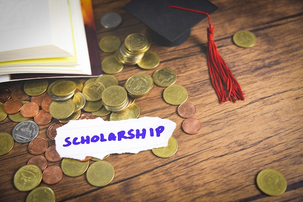 Moneda de dinero en madera con fondo oscuro y gorro de graduación en libro abierto