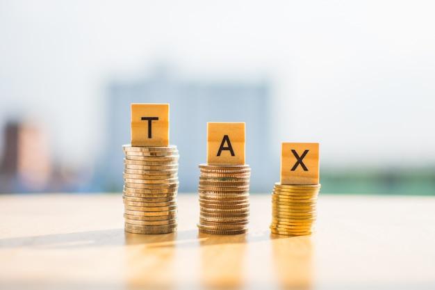 Moneda de dinero en la tabla de madera y el texto ahorra de impuestos con el fondo de la falta de definición.
