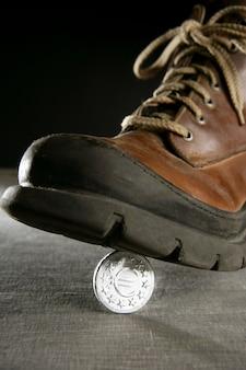 Moneda de euro moneda pisada por una bota