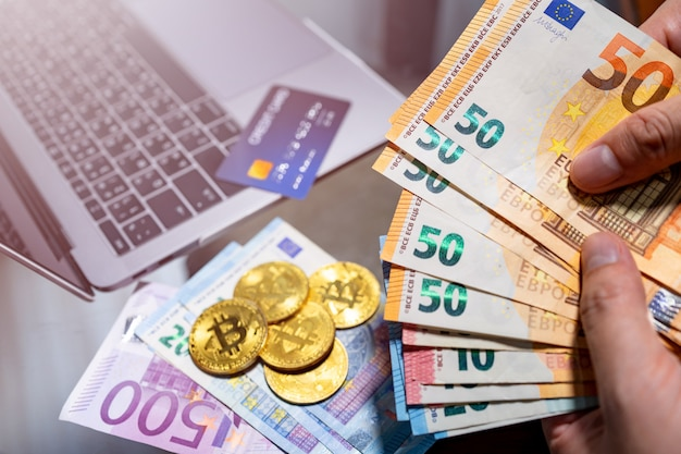 Moneda en euros y dinero electrónico bitcoin para compras en línea.