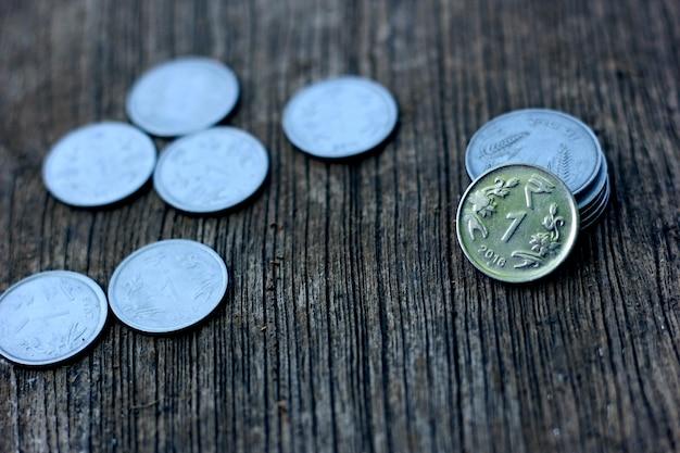 Moneda india en textura de madera,