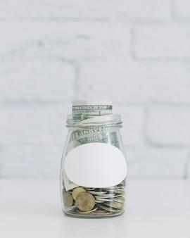 Moneda y monedas de dólar en un recipiente de vidrio abierto en la mesa