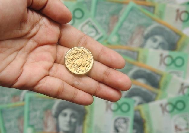 Moneda de oro australiana de un dólar en mano sobre cien billetes de fondo