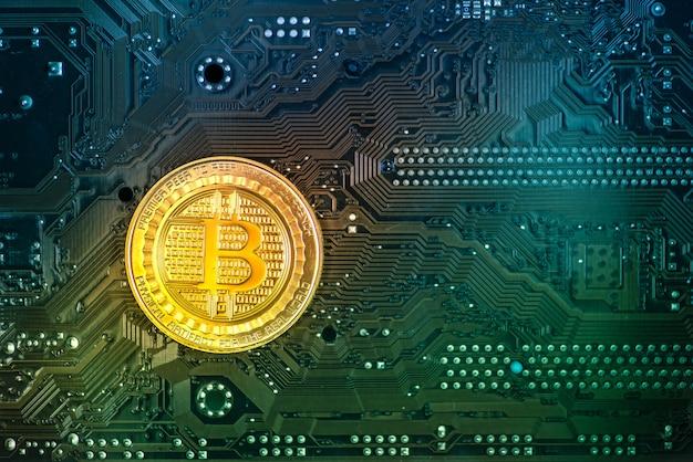 Moneda de oro bitcoin en una colorida placa de circuito. fondo azul-verde