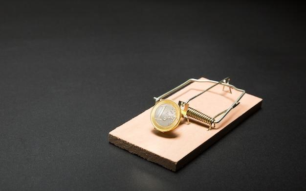 Moneda de oro en trampa para ratones
