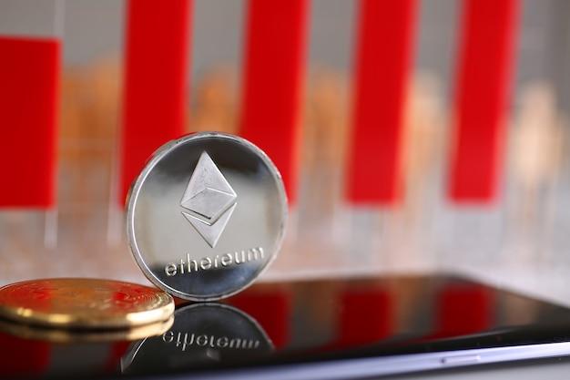 La moneda de plata ethereum yace en el teléfono celular
