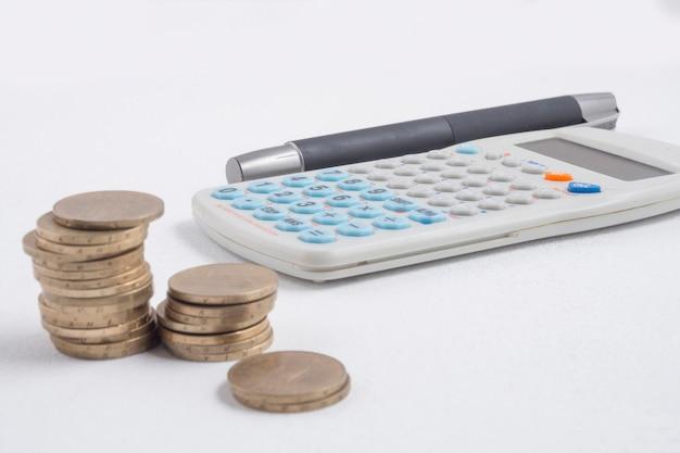 Monedas al lado de calculadora y bolígrafo