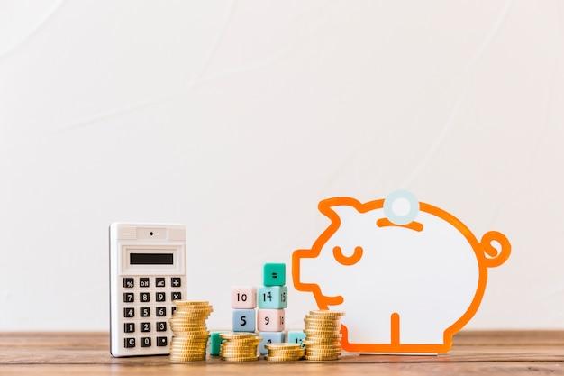 Monedas apiladas, bloques de matemáticas, calculadora y alcancía en la mesa de madera