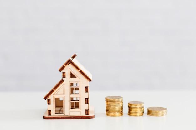 Monedas apiladas y casa de madera