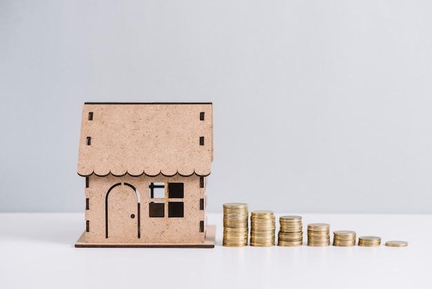 Monedas apiladas cerca de la casa modelo contra el fondo blanco