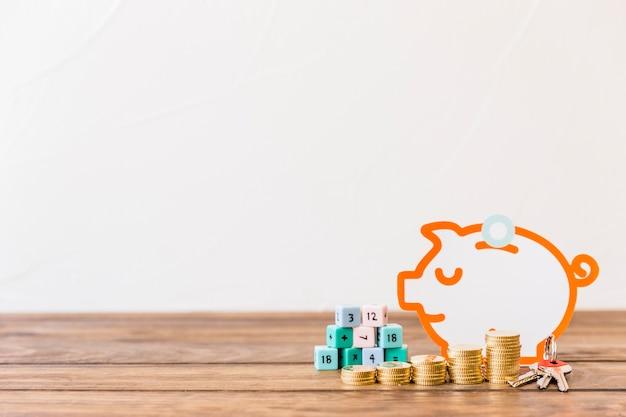 Monedas apiladas, clave, bloques de matemáticas y piggybank en el escritorio de madera