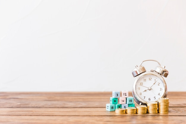 Monedas apiladas, despertador y bloques de matemáticas en la superficie de madera