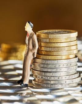 Monedas apiladas una encima de la otra con una figura humana.