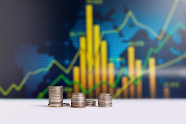 Las monedas apiladas con un gráfico estadístico en la parte posterior.