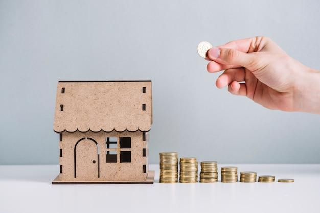 Monedas apiladas a mano de una persona cerca del modelo de la casa