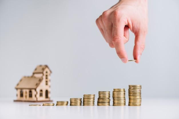 Las monedas apiladas a mano de una persona en frente del modelo de la casa