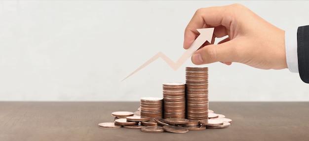 Monedas apiladas unas sobre otras en diferentes posiciones, mano en dinero casual de negocios