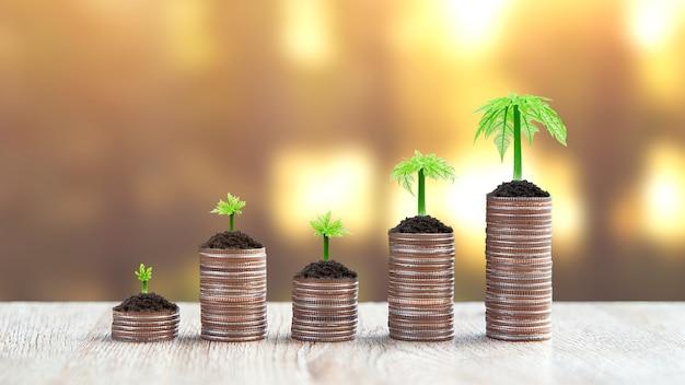 Las monedas se apilan en forma de gráfico con el retoño de un árbol en crecimiento